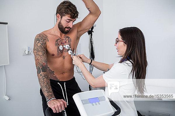 Krankenschwester führt EKG-Test am Patienten im Sprechzimmer durch