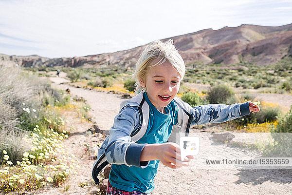 Junge rennt mit Blume in der Hand  Red Rock Canyon  Cantil  Kalifornien  Vereinigte Staaten