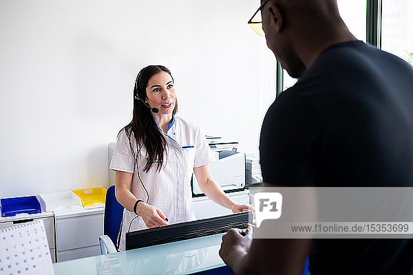 Patient speaking with nurse at hospital reception