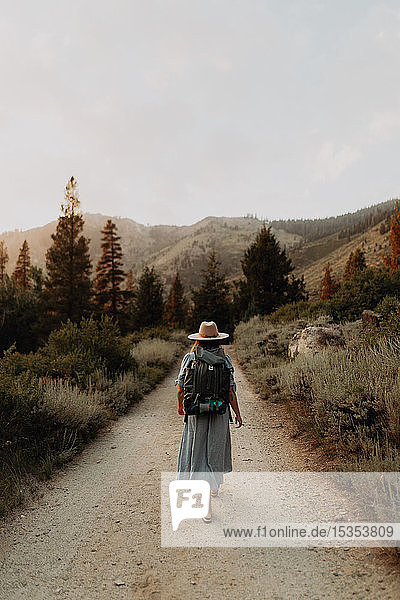 Young woman in maxi dress wearing backpack walking along rural road  rear view  Mineral King  California  USA