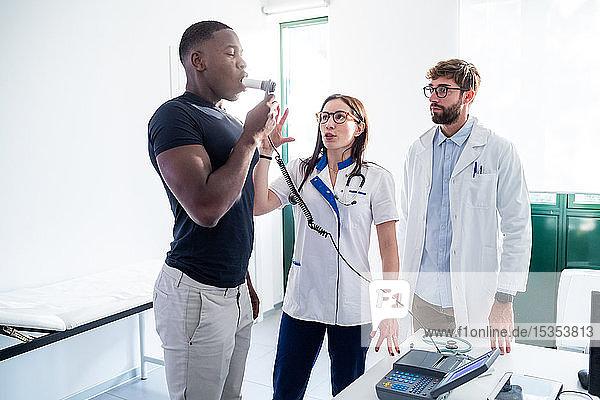 Ärzte beobachten  wie ein Patient im Krankenhaus in ein Beatmungsgerät geblasen wird