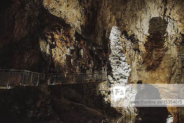Tourists views stalagmites in an underground cave; Italy