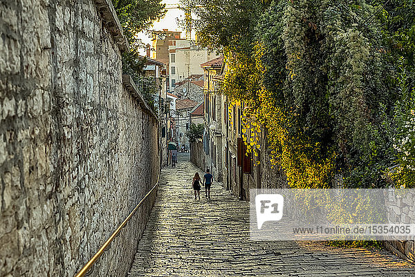 Couple walking down a narrow street holding hands; Pula  Istria  Croatia