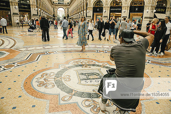 A woman in a dress poses for a photographer in the Galleria Vittorio Emanuele II shopping mall; Milan  Italy