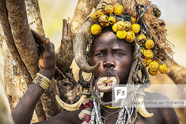Mursi woman wearing a lip plate in a village in Mago National Park; Omo Valley  Ethiopia