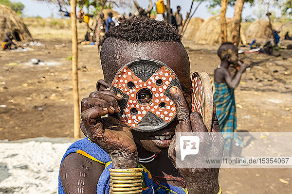 Mursi boy showing a lip plate in a village in Mago National Park; Omo Valley  Ethiopia