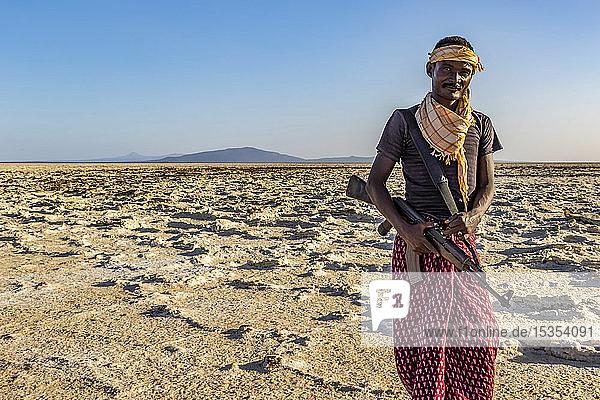 Afar man carrying a gun in the salt flats of Lake Karum (Lake Assale)  Danakil Depression; Afar Region  Ethiopia
