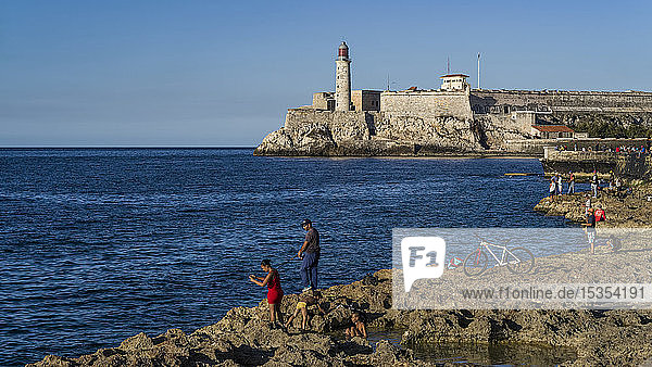 Fishing along the coast with Morro Castle in the distance; Havana  Cuba