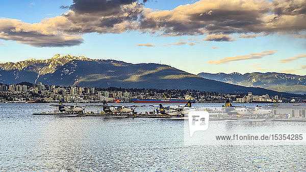 Float planes in a harbour at dusk; Vancouver  British Columbia  Canada