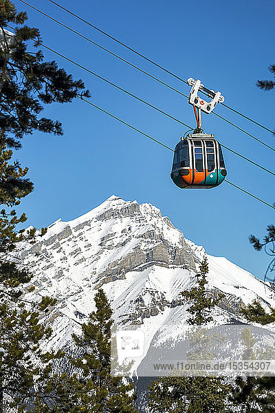 Gondola pod travelling along cables with snow covered mountain and blue sky in the background framed by evergreen trees  Banff National Park; Banff  Alberta  Canada