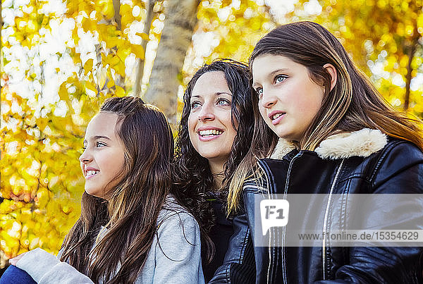 A mother with her two daughters enjoying beauty in nature together in a city park on a warm autumn afternoon: Edmonton  Alberat  Canada