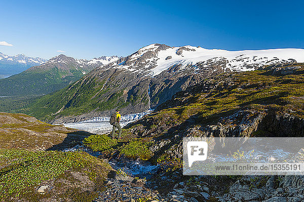 A man backpacking near a small stream in Kenai Fjords National Park with Exit Glacier in the background on a sunny summer day in South-central Alaska; Alaska  United States of America