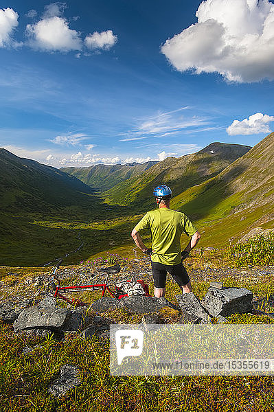 A man pausing for a rest while riding his mountain bike on the Palmer Valley Road near Hope  Alaska on a sunny summer day in South-central Alaska; Alaska  United States of America