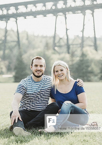 Portrait of couple in a park sitting on the grass with a bridge in the background; Edmonton  Alberta  Canada