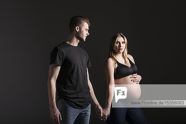 A young expectant couple holding hands with the mother looking at the camera in a studio on a black background: Edmonton,  Alberta,  Canada