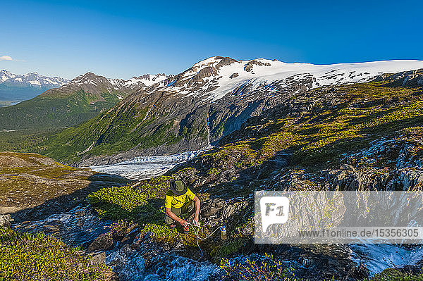 A man backpacking and filling his water bottle from a small stream in Kenai Fjords National Park with Exit Glacier in the background on a sunny summer day in South-central Alaska; Alaska  United States of America