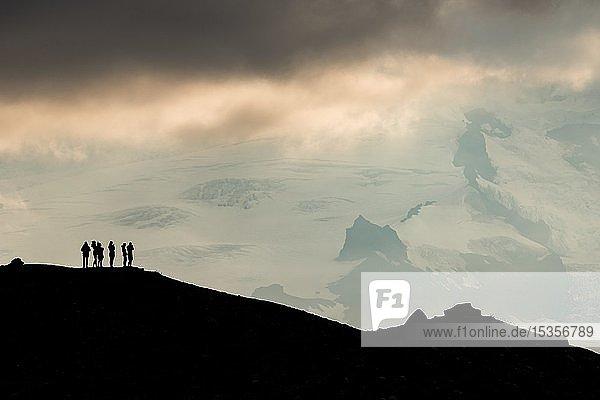 Silhouette von Touristen am Bergkamm mit Blick auf Hvannadalshnúkur und Gletscher Öræfajökull  Südisland  Island  Europa