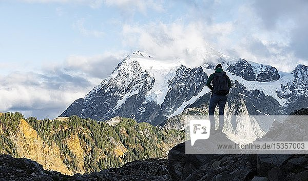Wanderin im Gegenlicht blickt in die Ferne  Tabletop Mountain  Ausblick auf Gletscher Mt. Shuksan mit Schnee  Mt. Baker-Snoqualmie National Forest  Washington  USA  Nordamerika