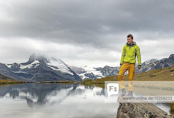 Wanderer steht auf Fels  Stellisee  hinten Matterhorn  wolkenverhangen  Wallis  Schweiz  Europa