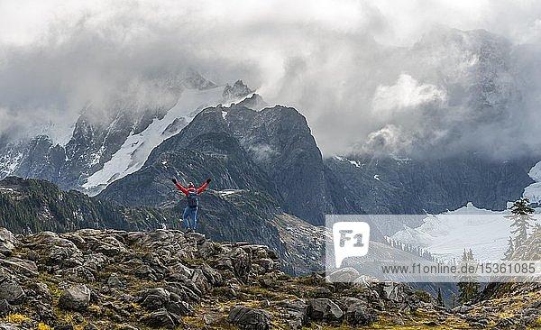 Wanderin streckt Arme in die Luft  Ausblick auf Mt. Shuksan mit Schnee und Gletscher  Wolkenhimmel  Mt. Baker-Snoqualmie National Forest  Washington  USA  Nordamerika
