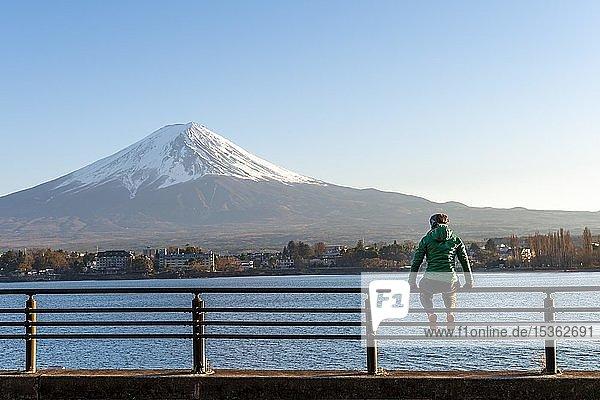 Junge Frau sitzt auf einem Geländer  Blick über Kawaguchi-See  hinten Vulkan Mt. Fuji  Präfektur Yamanashi  Japan  Asien