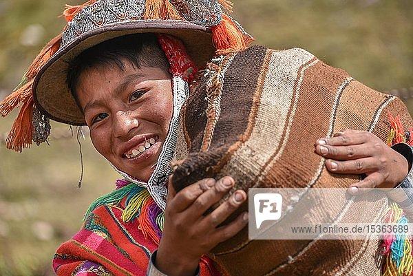 Indio Junge mit Hut mit bunten Bändern und Poncho trägt Sack mit Kartoffeln  Portrait  bei Cusco  Peru  Südamerika
