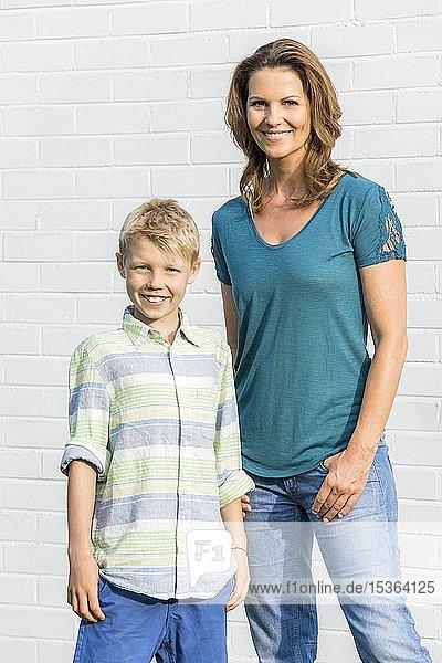 Mutter und Sohn stehen vor einer weißen Wand  schauen in die Kamera  lächeln  Deutschland  Europa