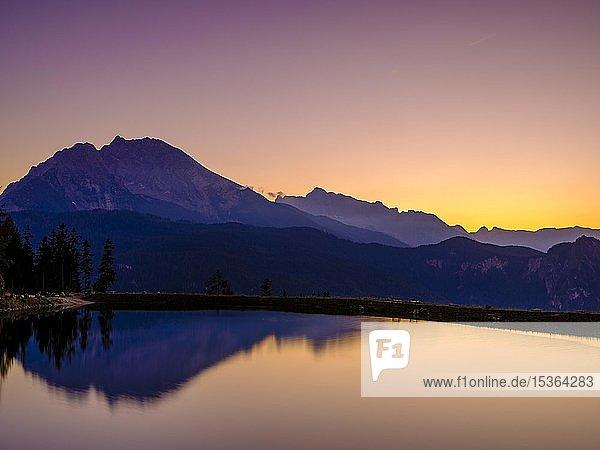 Bergsilhouetten spiegeln sich in einem künstlichen Bergsee bei Sonnenuntergang  Watzmann  Hochkalter  Berchtesgadener Alpen  Nationalpark Berchtesgaden  Schönau am Königssee  Berchtesgadener Land  Oberbayern  Bayern  Deutschland  Europa