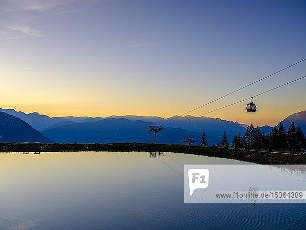 Alpenpanorama  Gondel der Seilbahn Jennerbahn spiegelt sich im Abendlicht in einem künstlichen Bergsee  Jenner  Berchtesgadener Alpen  Schönau am Königssee  Berchtesgadener Land  Oberbayern  Bayern  Deutschland  Europa