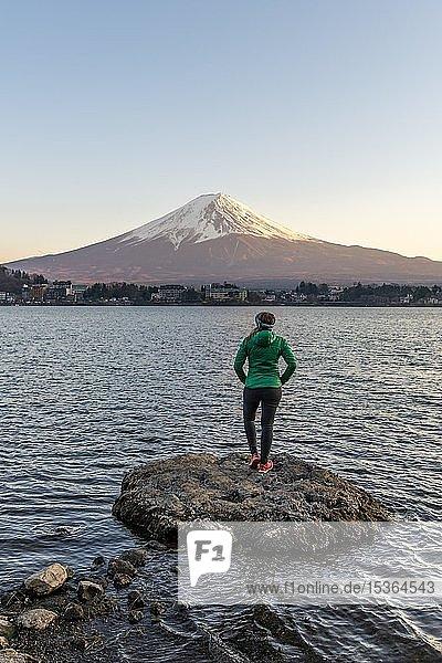 Abendstimmung  Junge Frau steht auf einem Stein im Wasser und blickt in die Ferne  Blick über Kawaguchi-See  hinten Vulkan Mt. Fuji  Präfektur Yamanashi  Japan  Asien