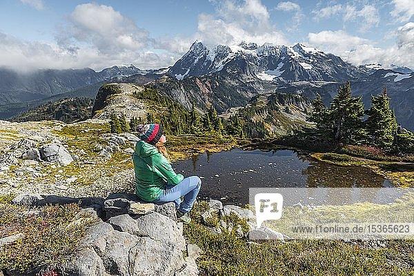Wanderin rastet auf einem Stein an kleinem Bergsee  Ausblick vom Tabletop Mountain auf Mt. Shuksan mit Schnee und Gletscher  Mt. Baker-Snoqualmie National Forest  Washington  USA  Nordamerika