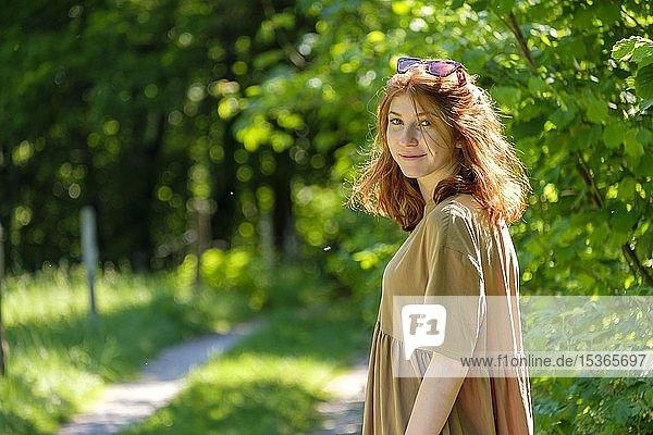 Junge rothaarige Frau im Wald  auf einem Weg  Oberbayern  Deutschland  Europa