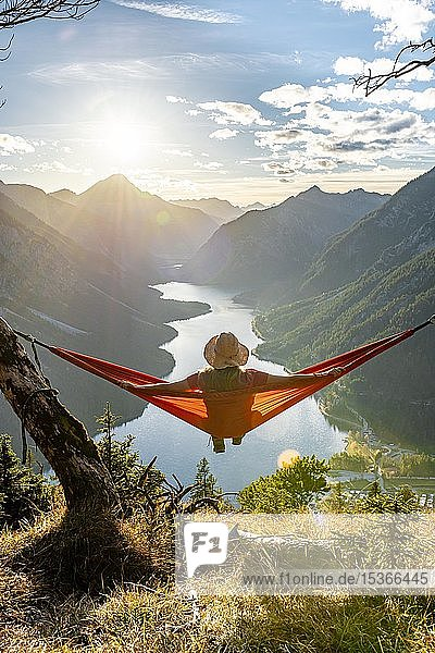 Frau mit Sonnenhut sitzt in einer orangen orangen Hängematte  Panoramablick auf Berge mit See  Plansee  Tirol  Österreich  Europa