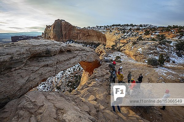 Tourists  photographers taking pictures of Mesa Arch at sunrise  view at Grand View Point Trail  Island in the Sky  Canyonlands National Park  Moab  Utah  USA  North America