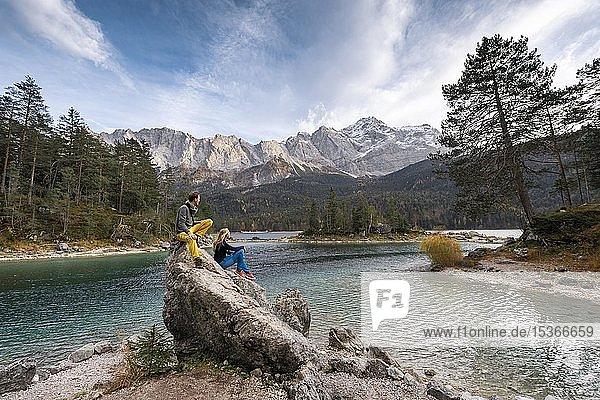 Zwei Wanderer sitzen auf einem Felsen am Ufer,  Blick in die Ferne,  Eibsee vor Zugspitzmassiv mit Zugspitze,  Wettersteingebirge,  bei Grainau,  Oberbayern,  Bayern,  Deutschland,  Europa