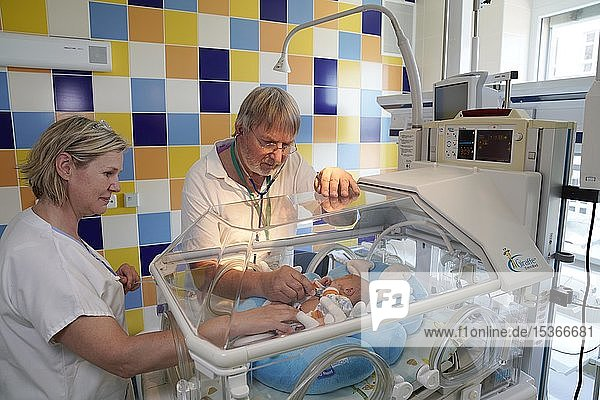 Arzt und Krankenschwester bei einer Untersuchung eines Neugeborenen im Brutkasten  Intensivstation für Neugeborene  Karlsbad  Tschechien  Europa