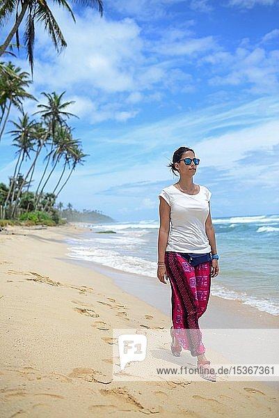 Junge Frau spaziert am Strand zwischen Weligama und Ahangama  Sri Lanka  Asien