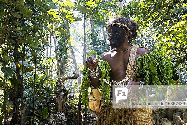 Traditionell gekleideter Mann mit schwarz bemaltem Gesicht im Dschungel  Ekasup Kulturdorf  Efate  Vanuatu  Ozeanien