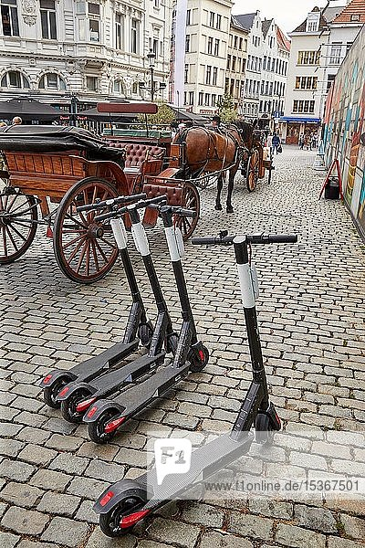 Elektroroller zum Mieten neben einer Pferdekutsche auf dem Grote Markt in Antwerpen  Belgien  Europa
