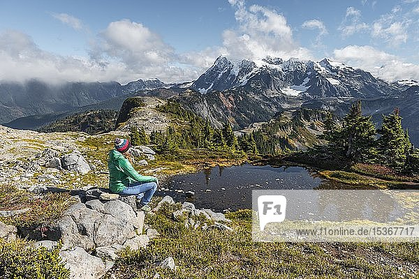 Wanderin rastet auf einem Stein an kleinem Bergsee  Ausblick vom Tabletop Mountain auf Mt. Shuksan mit Schnee und Gletscher  Mt. Baker-Snoqualmie National Forest  Washington  USA  Nordamerika