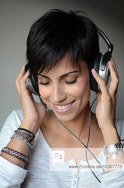 Junge Frau hört Musik über Kopfhörer  Portrait  Spanien  Europa