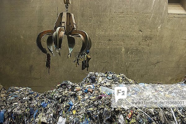 Gripper arm over pile of trash  crane transports waste in a waste incineration plant  TREA Breisgau  Eschbach  Baden-Württemberg  Germany  Europe