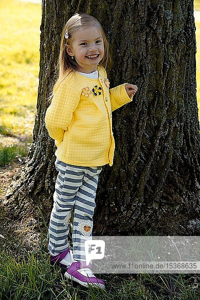 Kleines Mädchen lehnt lachend an Baumstamm  Tschechien  Europa