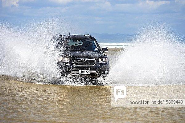 Schwarzer Hyundai Santa Fe 4x4 Geländewagen fährt am Strand des Ninety Mile Beach im Wasser,  Far North District,  Northland,  Nordinsel,  Neuseeland,  Ozeanien