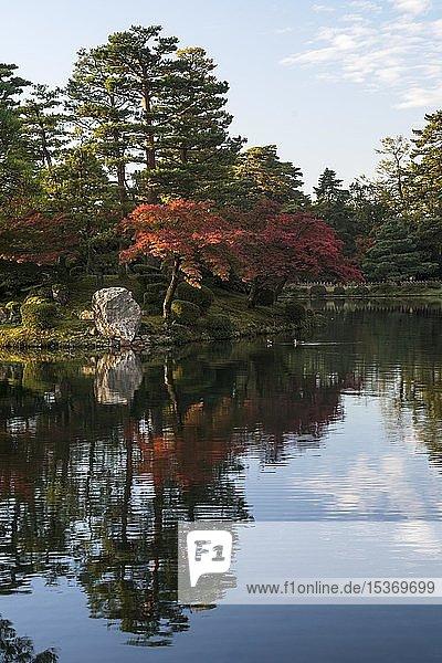Bäume mit rotem Herbstlaub am Wasser  Kenroku-en Garten  Kanazawa  Japan  Asien