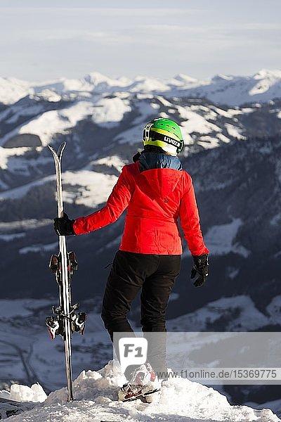 Skifahrerin mit Skihelm steht mit Ski an der Skipiste über dem Tal  blickt in die Ferne  hinten Berge  SkiWelt Wilder Kaiser  Brixen im Thale  Tirol  Österreich  Europa
