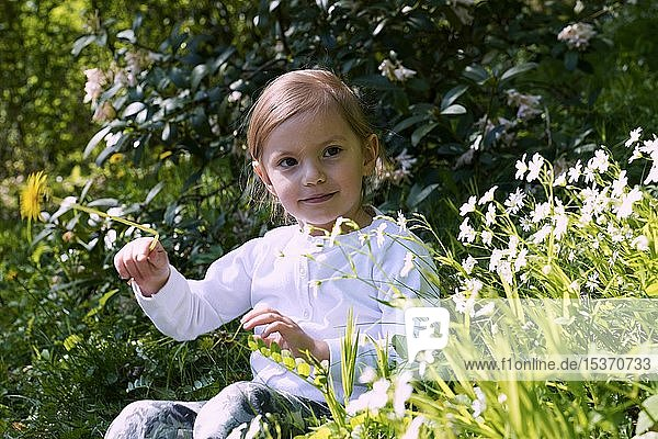 Kleines Mädchen sitzt zwischen Blumen auf der Wiese  Tschechien  Europa