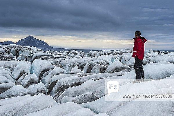 Tourist  Mann auf dem Eisfall eines riesigen Gletschers in Hornsund  Arktis  Spitzbergen  Norwegen  Europa