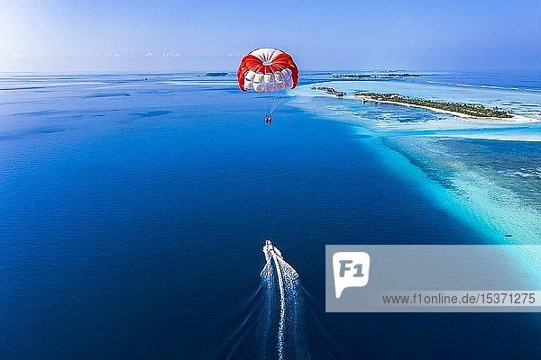 Luftaufnahme  Paraglider fliegt entlang eines Atolls der Malediven  Süd-Male-Atoll  Malediven  Asien