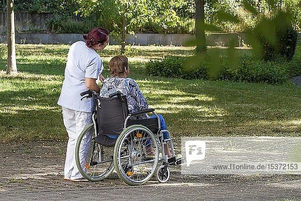 Frau sitzt im Rollstuhl  Pflegerin bei Spaziergang mit Frau im Rollstuhl  Deutschland  Europa